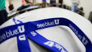 A lanyard with the see blue. U printed down the side lays on a table in front of an out of focus room of people.